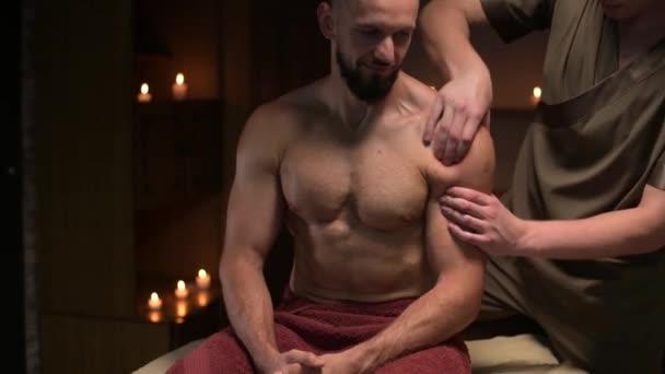 Ein männlicher Masseur führt einem muskulösen männlichen Athleten in einem Raum mit kontrastierendem dunklen Licht eine sportliche Schultermassage durch. Professionelle Sportmassage