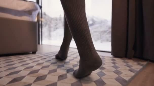 Alacsony szögű, széles szögű, harisnyás lány sétál át a hálószobán egy vidéki házban, az ágy mellett, panorámás ablakokkal. Kényelem vidéki vendégházakban a téli erdőben