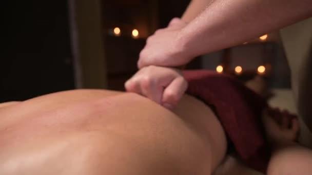 Mladý masér provádí sportovní masáž svalnatému sportovci. Profesionální masáž zad v tmavém pokoji se svíčkami. Relaxační a lázeňské zotavení svalového aparátu