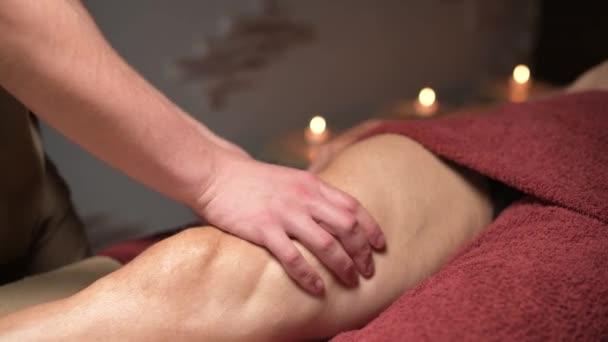 close-up Profesionální sportovní masáž kyčlí. Samec masér masíruje samce sportovce v místnosti s tlumeným světlem na pozadí hořících svíček.