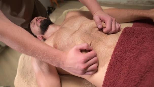 Detailní masážní aktivace bránice u mužského atleta. Profesionální sportovní masáž vnitřních orgánů