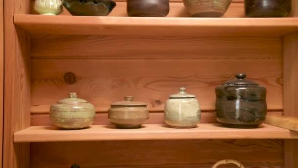 Yixing hliněná konvice pro ruční přípravu čaje obřad vedle další hliněné nádobí na dřevěné polici v místnosti