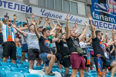 ODESSA, UKRAINE - August 3, 2018: emotional football fans support team at stadium during game in the football club Djurgardens IF Sweden game UEFA Europa League. Crowd football fans in stadium  soccer