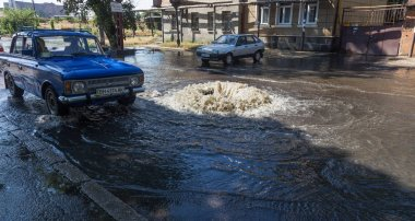 Odessa, Ukraine -3 July  2018: Driving cars on a flooded road during floods caused by rain storms. Cars float on water, flooding streets. Splash on the machine. Flooded city road with a big puddle