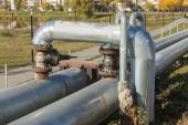 Fotografie moderne erhöhte Wärmerohre. Pipeline oberirdisch, die Wärme zur Beheizung der Stadt leitet. städtische Wärmeleitung in Metallisolierung in Wohnviertel der Stadt. offene Verlegung auf Säulen. Kommunale Wärmeversorgung