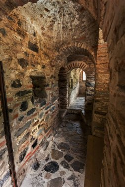 A narrow stone staircase in the tower of a medieval castle ancient Christian monastery of Rila, Bulgaria. Mysterious gloomy tunnel with walls of stone