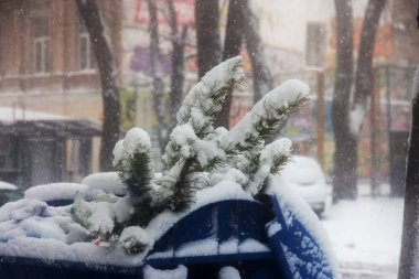 Strong snowfall in city streets in winter. Cars are covered with snow, slippery road. Bad weather in winter: heavy snow and blizzard. Pedestrians go under heavy snow. Winter and snowstorm, snowfall