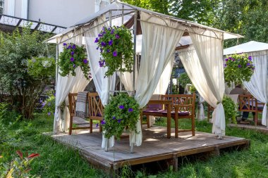 Street cafe under a canopy on a wooden platform located on the green with fresh grass in the city park and decorated with fresh flowers.