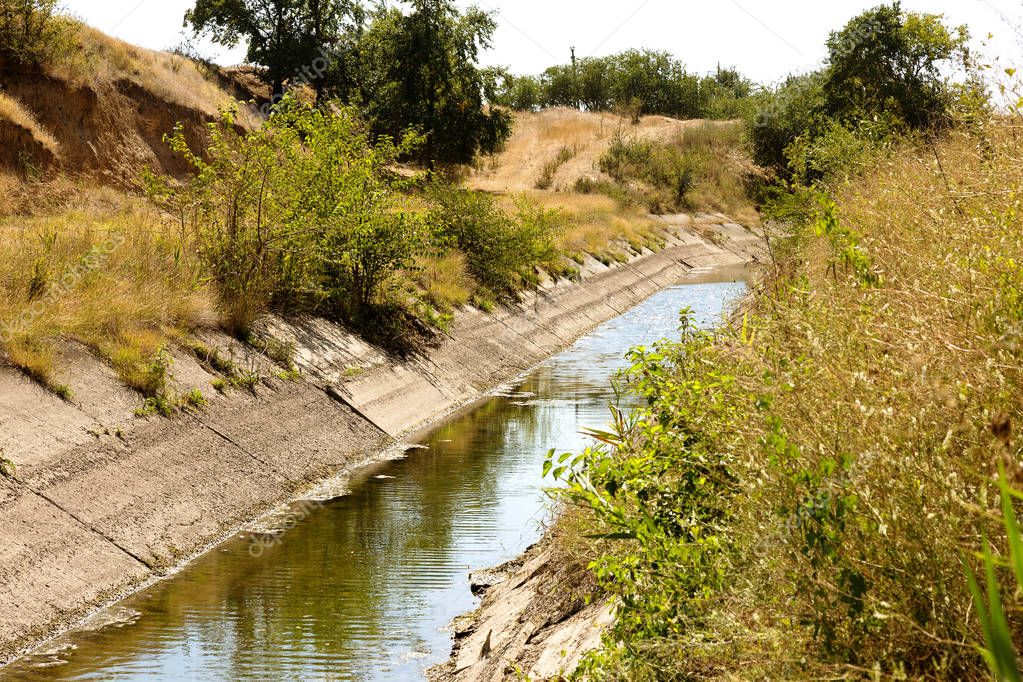 An old drying up irrigation channel with remains of water at bottom of canal. Blockade of water irrigation artery of Crimea. Artificial drought, destruction, collapse in irrigated agriculture