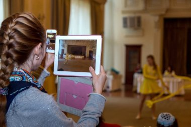 Odessa, Ukraine - October 25, 2015: A young woman taking pictures on the tablet performance athletes at sorenovaniyah gymnastics. Conceptual. Selective Focus