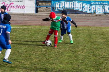 ODESSA, UKRAINE 0 April 1, 2018: Training of sports game for young children. Football soccer game for children. Young players of football players in sports club uniform, running and playing football