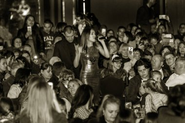 Odessa, Ukraine - April 8, 2019: crowd of spectators at rock concert by ALOSHA during music show. Crowds of happy people enjoy rock concert, raise their hands and clap their hands, spectators in stand