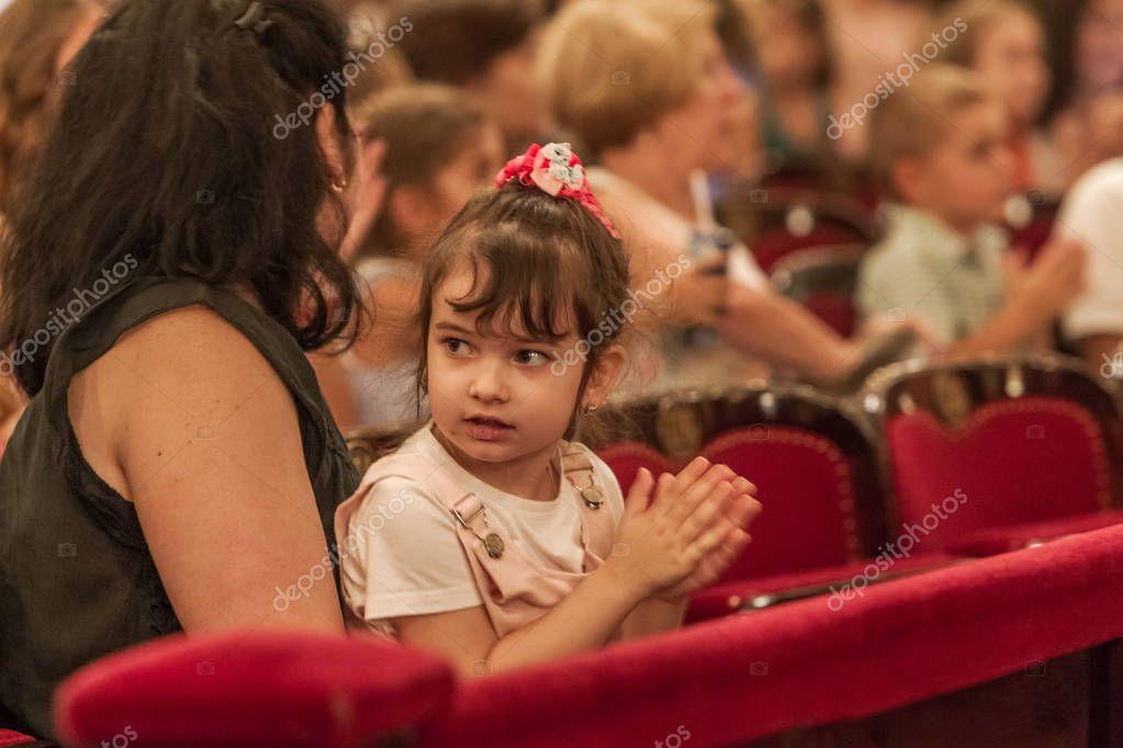 Odessa, Ukraine - CIRCA 2019: selective focus. Spectators children in theater during popular children's play. Children's Delight audience. Concert audience in motion. Children's spectators in theater stock vector