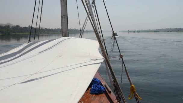 View across large wide river Nile in Egypt to riverbank through rural countryside landscape from luxury sailing cruise boat
