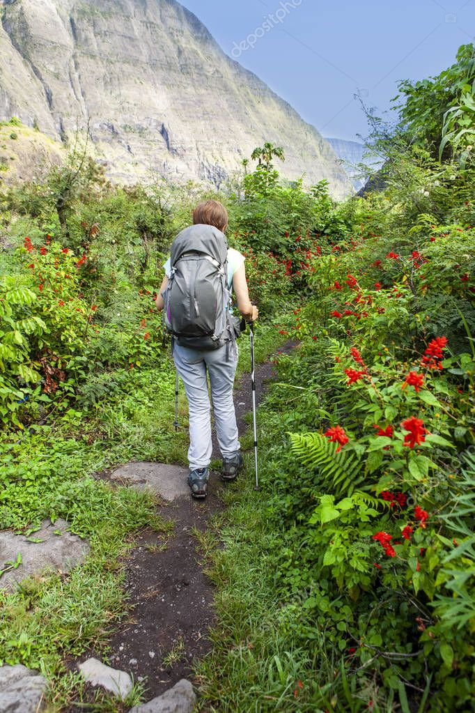 lonely woman hiking on a path lined with flowers