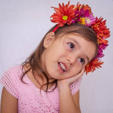 White girl and black eyes with natural flowers on her head, pink knitted dress and white background supports her head in a hand with ambiguous expressio