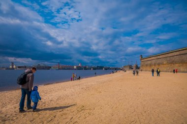 ST. PETERSBURG, RUSSIA, 17 MAY 2018: Unidentified people walking over the yellow sand in the beach of Peter and Paul Fortress in St.Petersburg during a sunny day in St. Petersburg