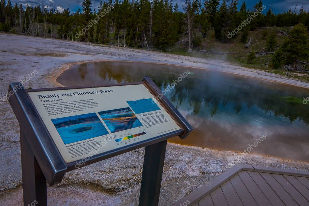 YELLOWSTONE, MONTANA, USA MAY 24, 2018: Informative sign of chromatic pools at hot spring and orange microbial mat in the old faithful geyser basin of Yellowstone National Park, Wyoming