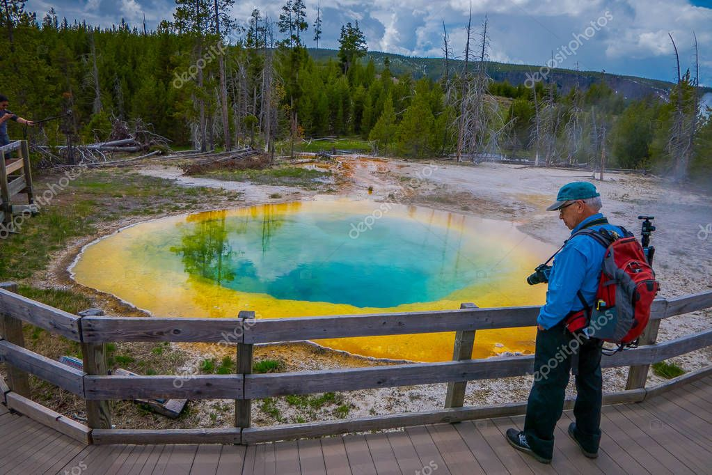 YELLOWSTONE, MONTANA, USA MAY 24, 2018: Outdoor view of tourists walking and taking picture of beautiful and colorful grand Prismatic Pool, at Yellowstone National Park in sunny day