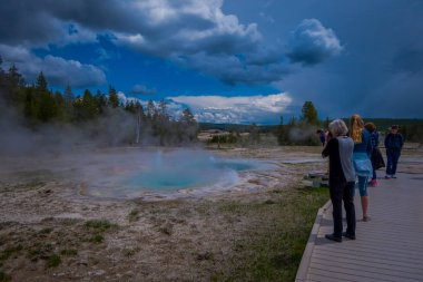 YELLOWSTONE, MONTANA, USA MAY 24, 2018: Unidentified tourists walking around the Old faithful geyser in Yellowstone National park on a boardwalk surrounded by vapor