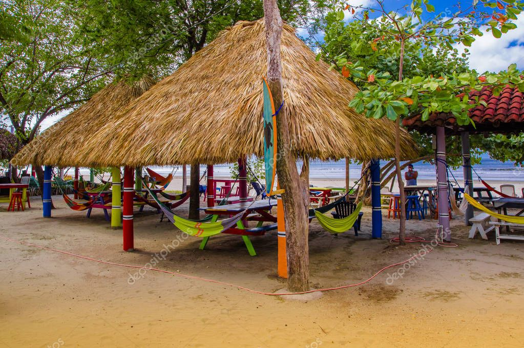 Playa hermosa, Mexico, May, 29, 2018: Outdoor view of hammocks inside of hut structures made of straw, in a caribbean Beach, suring a gorgeous sunny day in Playa hermosa