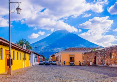 Ciudad de Guatemala, Guatemala, April, 25, 2018: View of antigua city, with some cars waiting over a toned pavement street, surrounding of old buildings, and the Agua volcano in the background