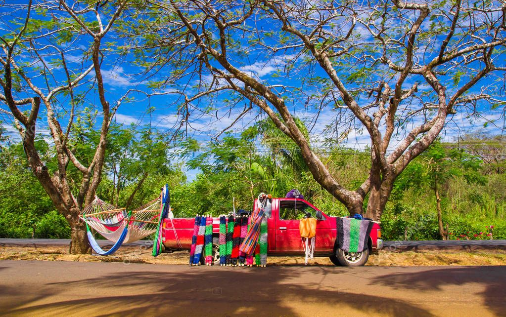 Samara, Costa Rica, June, 26, 2018: Red car selling hammocks and surrounding of nature of a gorgeous beach in Samara area in Costa Rica
