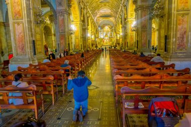 SANTIAGO, CHILE, OCTOBER 09, 2018: Unidentified people praying at interior of cathedral of Santiago de Compostela, the final destination for pilgrims walking along the world famous camino de Santiago.