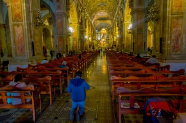 SANTIAGO, CHILE, OCTOBER 09, 2018: Unidentified people praying at interior of cathedral of Santiago de Compostela, the final destination for pilgrims walking along the world famous camino de Santiago