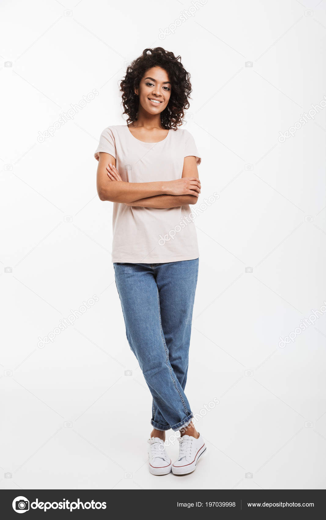 242b7d1508 Full length portrait of beautiful american woman wearing jeans and t-shirt  standing with arms folded and smile isolated over white background — Photo  by ...