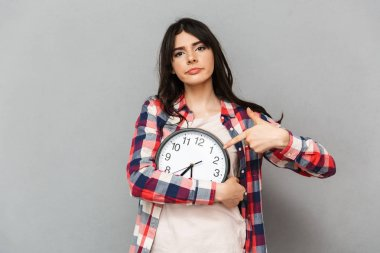 Image of displeased young lady standing isolated over grey background wall holding clock pointing.