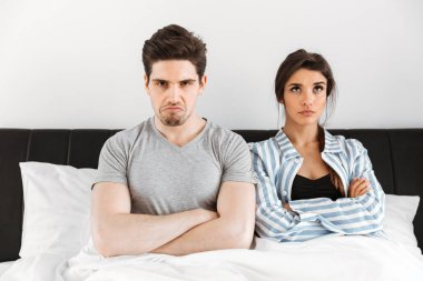 Upset young couple having a conflict while sitting in bed