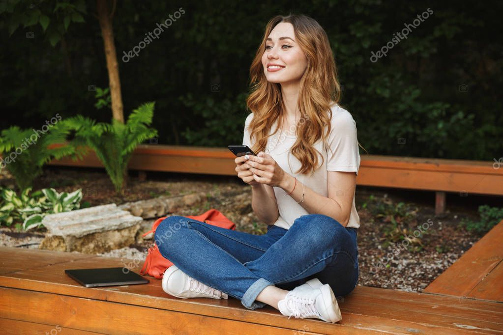 Cheerful young girl using mobile phone while sitting on a bench outdoors