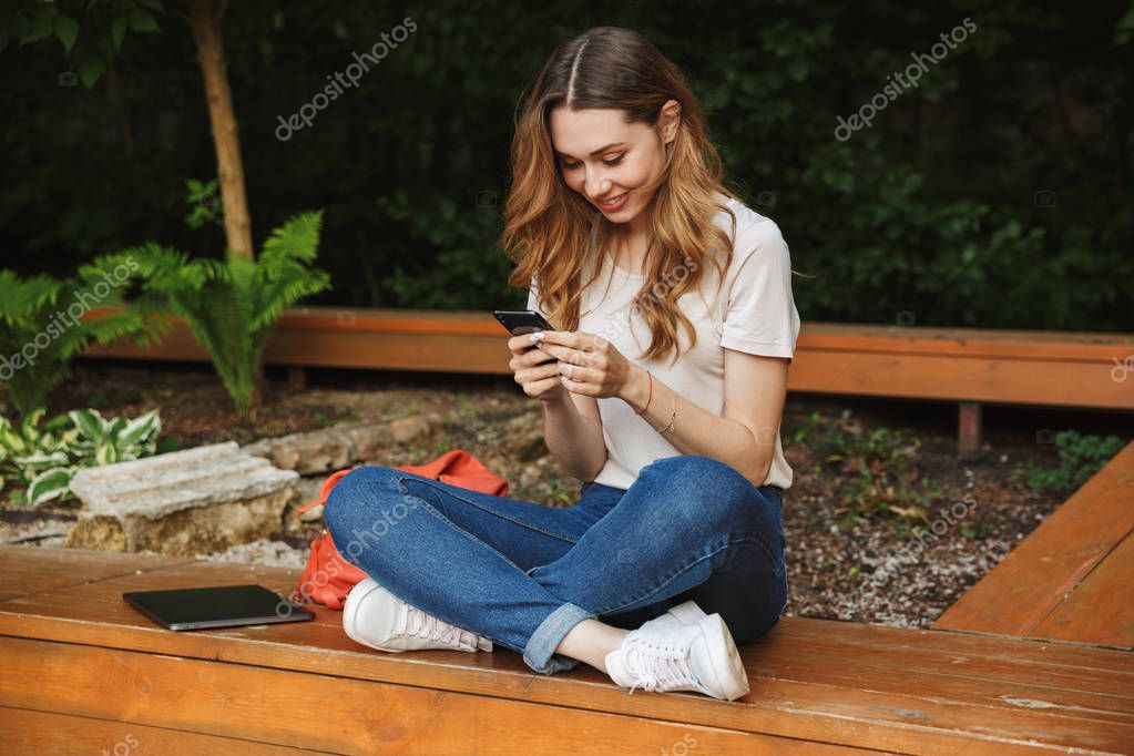 Lovely young girl using mobile phone while sitting on a bench outdoors