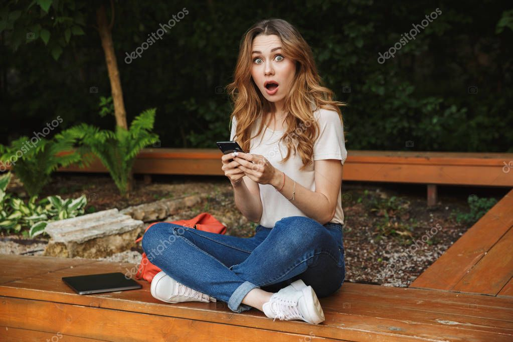 Surprised young girl holding mobile phone while sitting on a bench outdoors