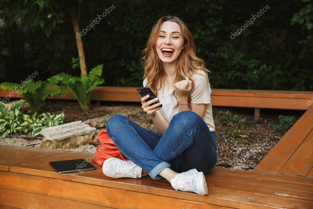 Satisfied young girl using mobile phone while sitting on a bench outdoors