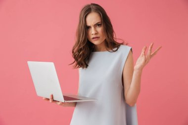 Image of confused young woman standing isolated over pink background using laptop computer. Looking camera.