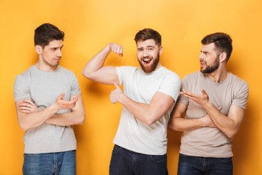 Two young envious men looking at their male friend isolated over yellow background