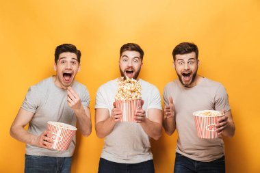 Three young cheerful men eating popcorn and celebrating isolated over yellow background