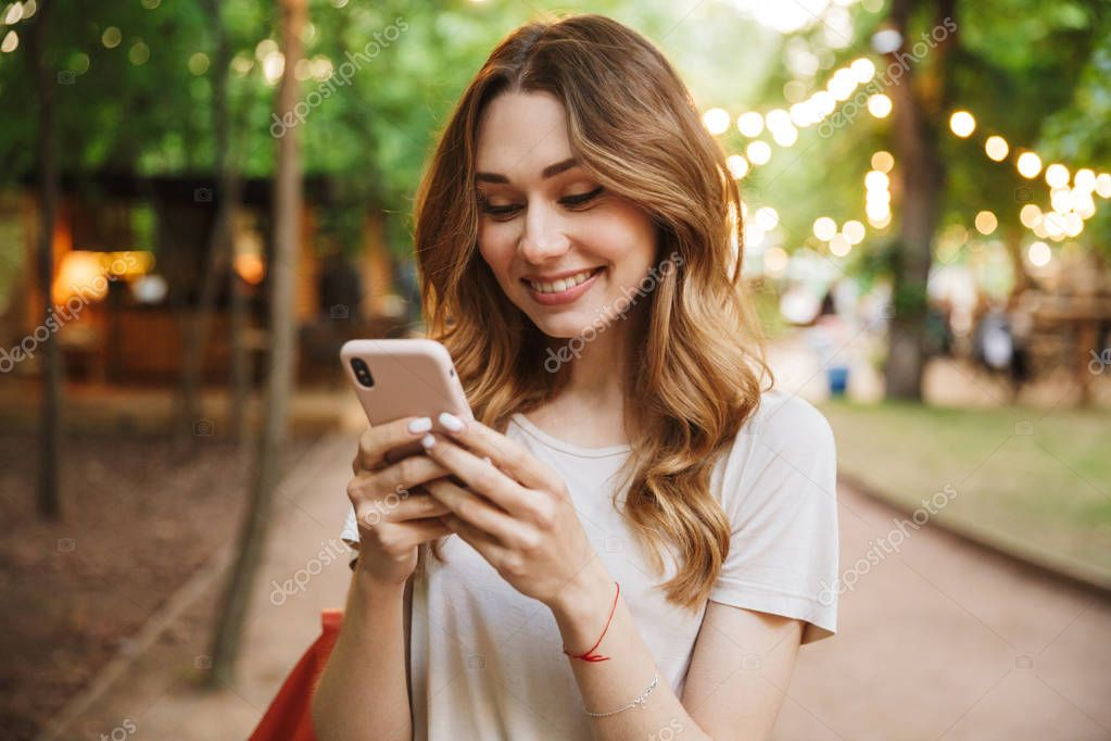 Smiling young girl holding mobile phone while standing at the park