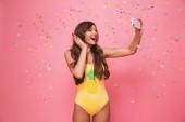 Fotografie Porträt von eine glückliche junge Frau gekleidet in Badeanzug, ein Selbstporträt unter Konfetti Regen über Rosa hintergrund isoliert