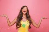 Fotografie Porträt einer fröhlichen jungen Frau gekleidet in Badeanzug Spaß unter Konfetti Regen über Rosa hintergrund isoliert