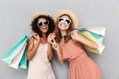 Fotografie Portrét dvou šťastné mladé ženy oblečené v letních šatech drží nákupní tašky a ukazuje míru gesto izolované nad šedým pozadím