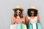 Portrait of two happy young women dressed in summer clothes looking inside shopping bags isolated over gray background