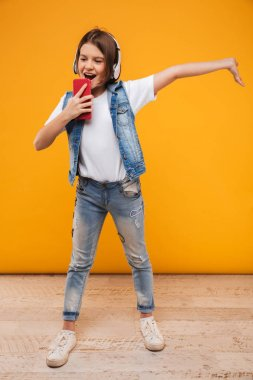 Full length portrait of a cheerful little schoolgirl listening to music with headphones and having fun over yellow background