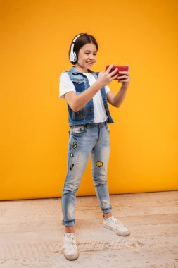 Full length portrait of a happy little schoolgirl listening to music with headphones while using mobile phone over yellow background