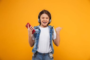 Portrait of an excited little schoolgirl listening to music with headphones while holding mobile phone over yellow background
