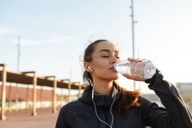 Image of beautiful young asian sports woman listening music with earphones drinking water outdoors.