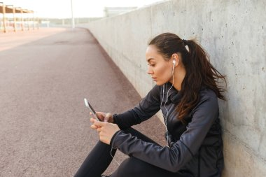 Image of serious young asian sports woman sitting outdoors listening music using mobile phone.