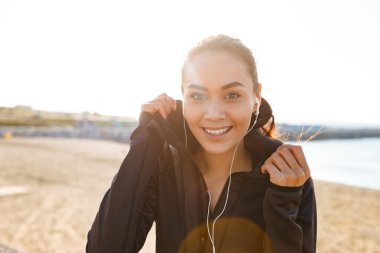 Photo of cheerful young asian sports woman sitting outdoors listening music looking camera.